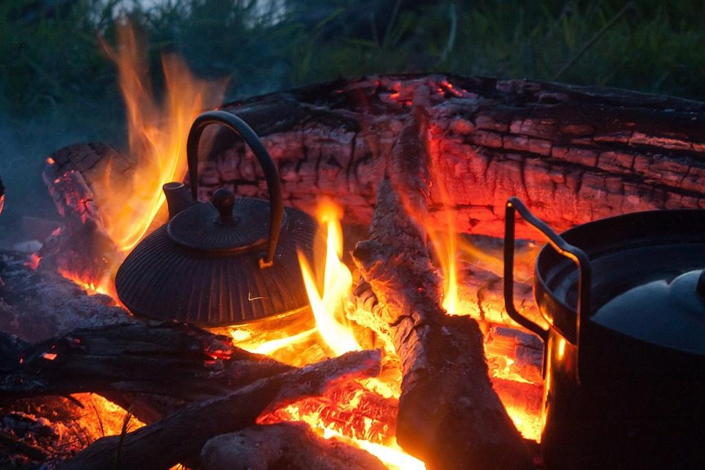 W płomieniach ogniska stoi żeliwny czajnik.