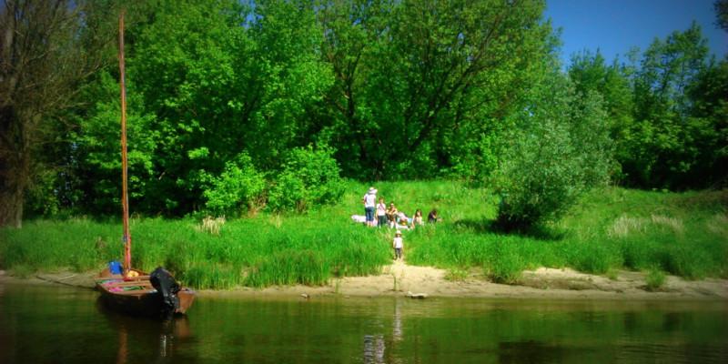Na wiślanym umajonym brzegu piknikuje kilkoro dorosłych z dziećmi. Obok stoi zacumowana łódź.