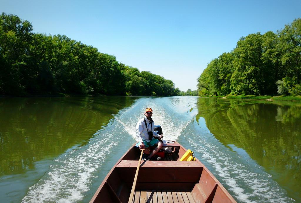 Widok na rufę łodzi z siedzącym sternikiem Jakubem Gołębiewskim. Widać wyraźny kilwater za łodzią. Z dwóch stron łodzi zwężają się w oddali dwie ściany drzew.