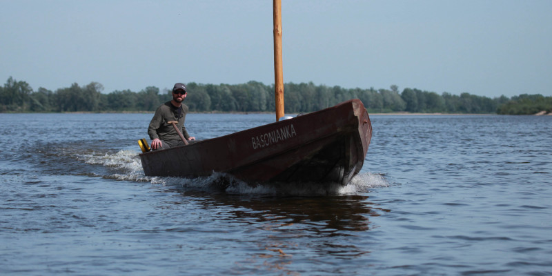 tradycyjna łódź wiślana Basonianka ze sternikiem Jakubem Gołębiewskim na pokładzie płynie w stronę widza